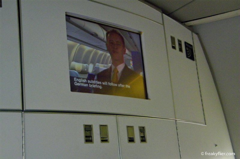 Lufthansa pre-flight safety briefing delivered in German and English with subtitles for both
