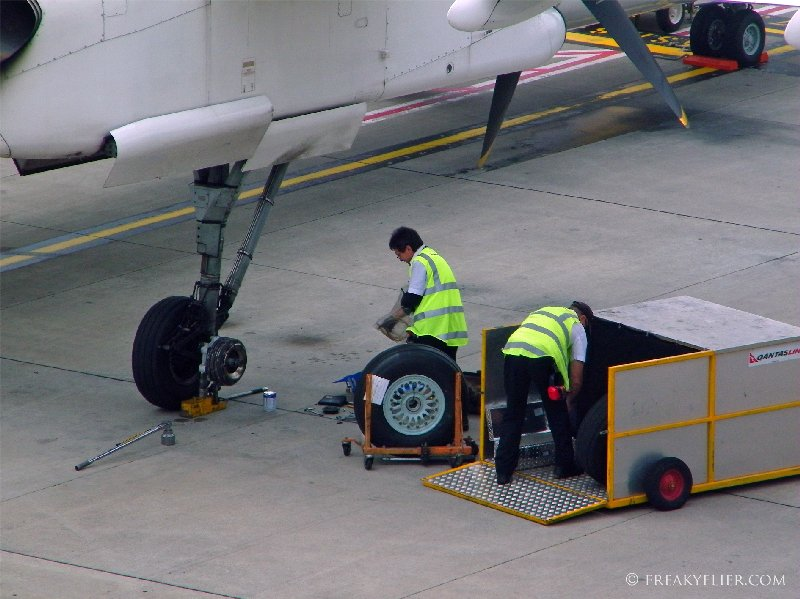 QantasLink Dash 8 Q400 undergoing a wheel change as seen from The Qantas Club Melbourne
