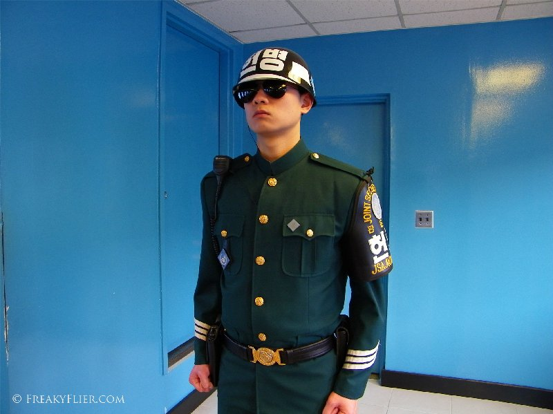 South Korean soldier stands guard at the northern door inside the blue building conference room