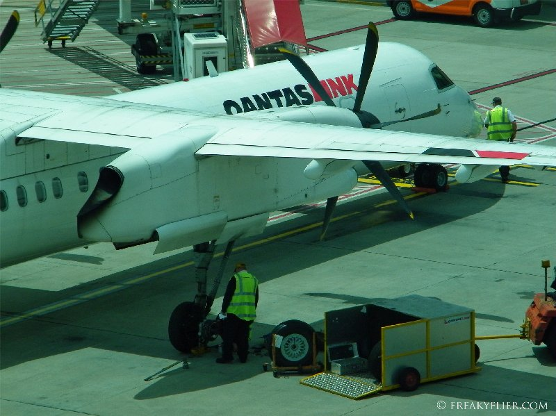 A QantasLink Dash-8 Q400 undergoes a wheel change at Melbournes Tullamarine Airport