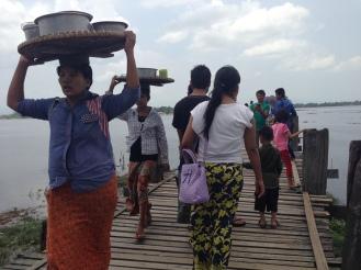 workers making their way across the U Bein Bridge